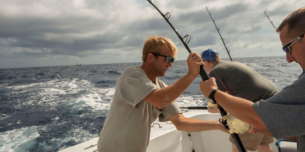 Longer Days Fishing Charter's mate helping client fight big yellowfin tuna on offshore charter at Cape Hatteras.
